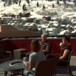 people enjoy sunny winter weather on the rooftop in park city utah